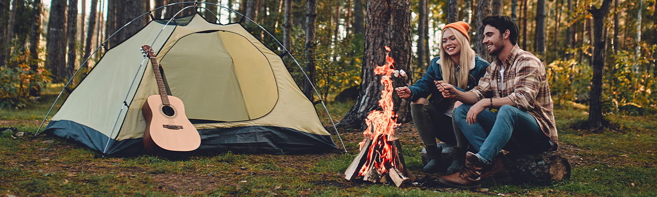 couple camping next to fire