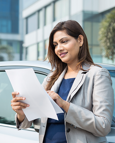 Woman reading her extended warranty paperwork by her car