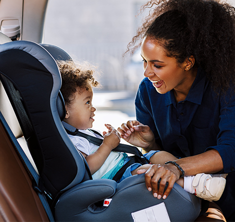 A woman getting her child in car-seat in the vehicle