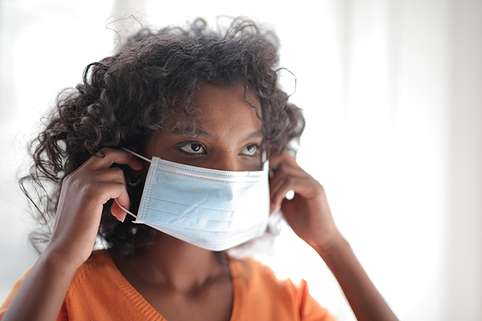 Young woman putting on facemask