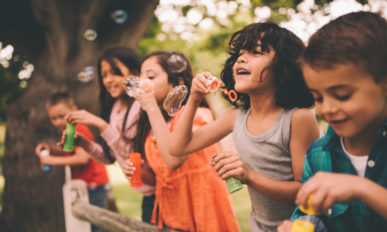 A group of diverse children playing and blowing bubbles