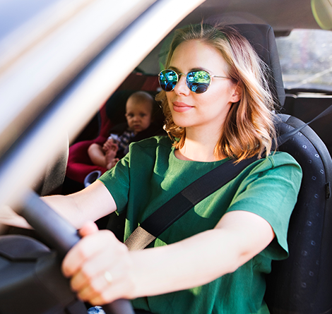 A woman with sunglasses in a car with her baby in the backseat