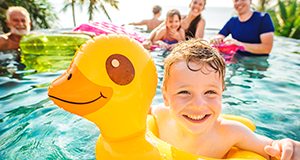 Boy in pool on yellow ducky float