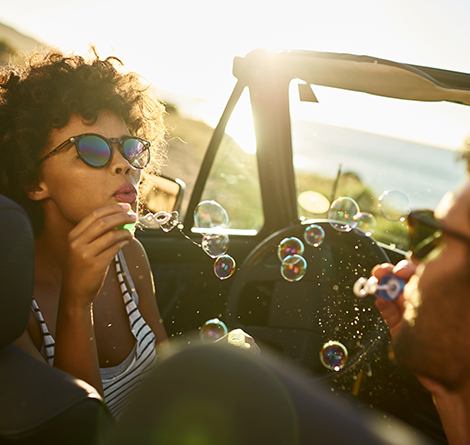 man and women blowing bubbles in convertible